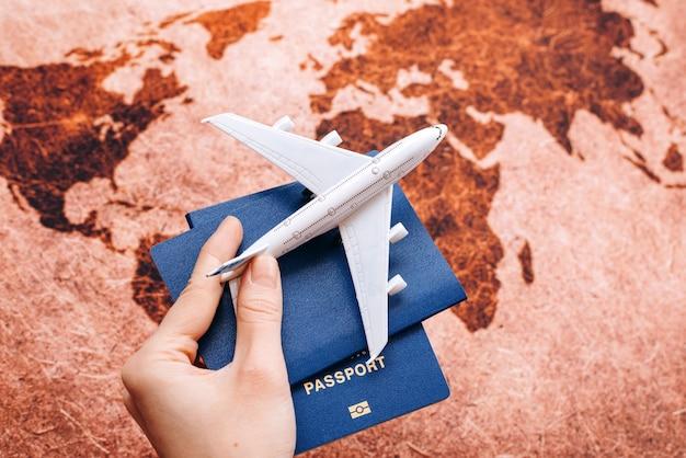 Mano che tiene il passaporto neutro sulla mappa del mondo