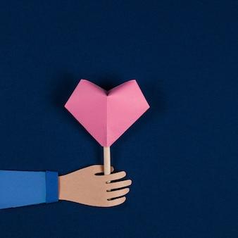 Mano che tiene il cuore di origami. biglietto di san valentino, taglio della carta. lay piatto, copia spazio. arte della carta di san valentino. vacanze, compleanno, concetto di san valentino. arte della carta e stile origami. formato quadrato