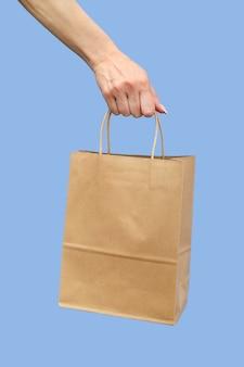 Mano che tiene un sacchetto di carta con manici su sfondo blu.