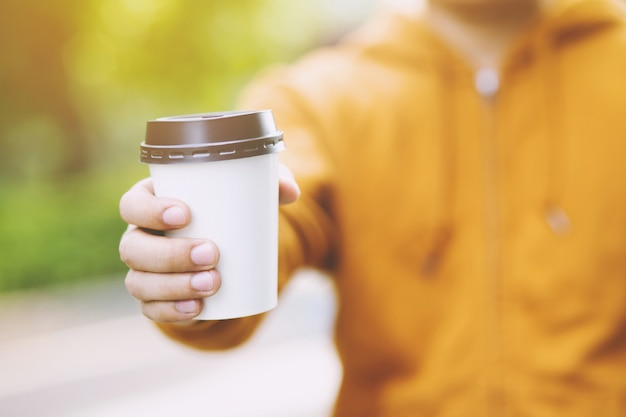 Mano che tiene il bicchiere di carta da asporto bere caffè sulla luce naturale del mattino. posto spazio per il tuo logo. lascia spazio per scrivere il testo.