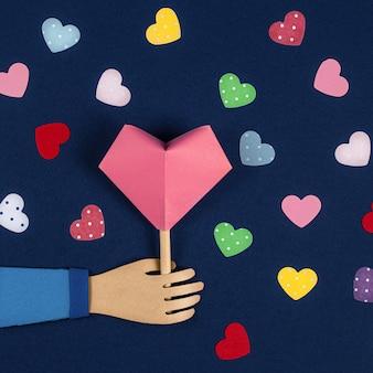 Mano che tiene un cuore di carta origami.