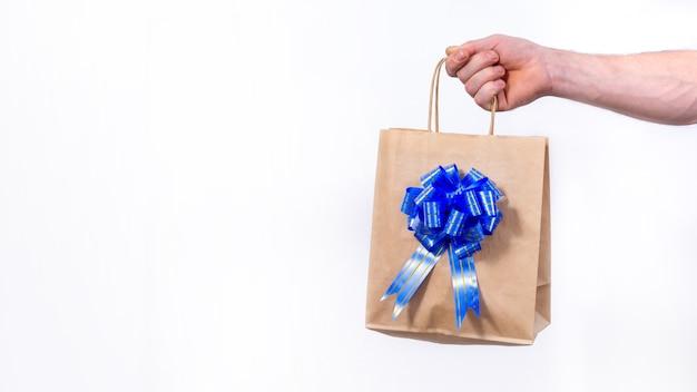Mano che tiene il sacchetto della spesa di carta con fiocco blu