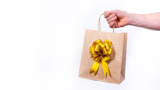 Mano che tiene il sacchetto della spesa di carta con fiocco dorato