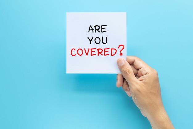 Mano che tiene la carta con la domanda sei coperto? isolato su sfondo blu con spazio di copia. concetto di assicurazione di viaggio