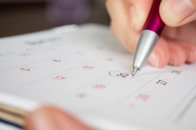 Mano che tiene il segno del cerchio della penna sulla data del calendario