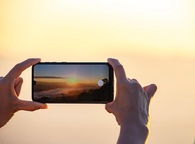 Mano che tiene il telefono che riprende il sole del mattino e la nebbia.
