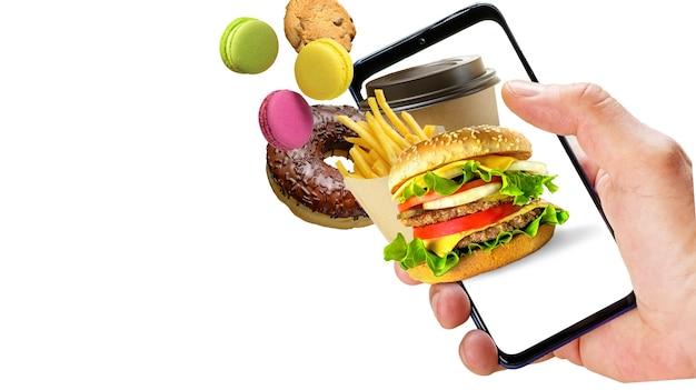 Mano che tiene il telefono con le ciambelle della tazza di caffè delle patatine fritte dell'hamburger che volano fuori dallo schermo isolato su fondo bianco. ordinazione online di fast food.