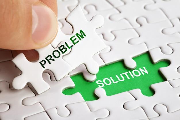 Mano che tiene un pezzo di puzzle con soluzione del problema di parola. foto di concetto di affari