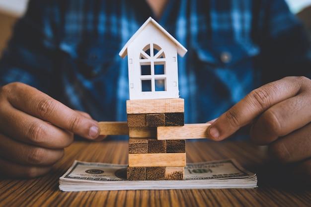Passi la tenuta del pezzo di blocco di legno con la casa bianca di modello sulla banconota del dollaro.