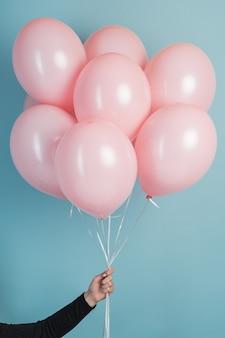 Mano che tiene gli aerostati di aria rosa