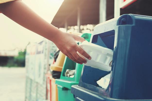 Mano che tiene maniglie di plastica discarica nella spazzatura