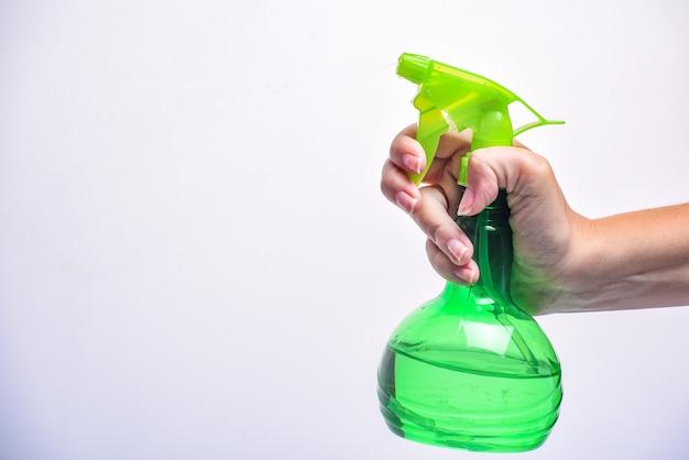 Mano che tiene la bottiglia di plastica spray verde su un bianco