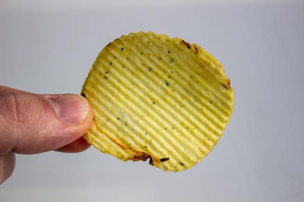 Mano che tiene le patatine fritte isolate su bianco.