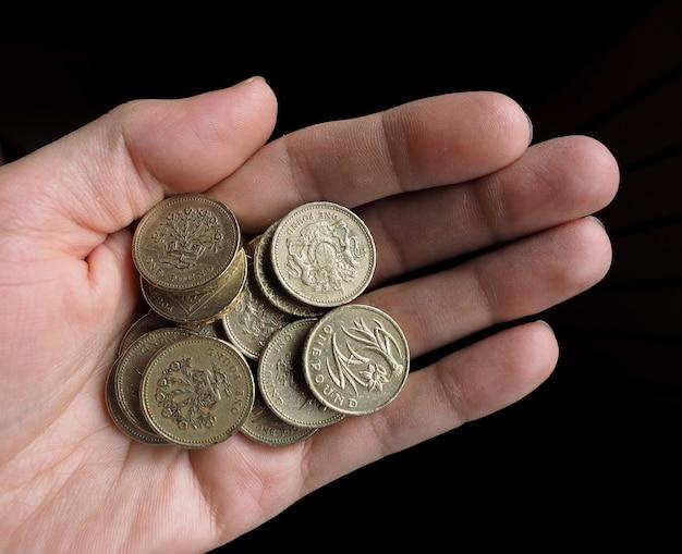 Mano che tiene le monete della sterlina