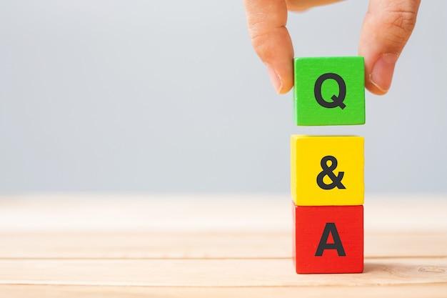 Mano che tiene q e una parola con un cubo di legno. faq (domande frequenti), risposta, domanda, informazioni, comunicazione e concetti di brainstorming