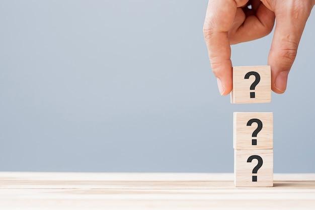 Mano che tiene il punto interrogativo (?) sul blocco cubo di legno sullo sfondo del tavolo. faq (domande frequenti), risposta, domande e risposte, informazioni, comunicazione e concetti di interrogazione