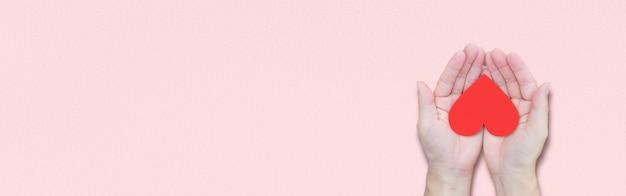 Mano che tiene cuore rosso su sfondo rosa. vista dall'alto, con spazio di copia. concetti di san valentino.