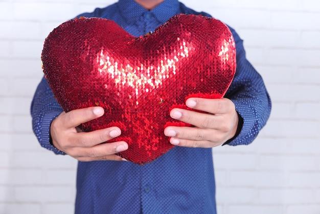 Mano che tiene il simbolo del cuore rosso su sfondo bianco.