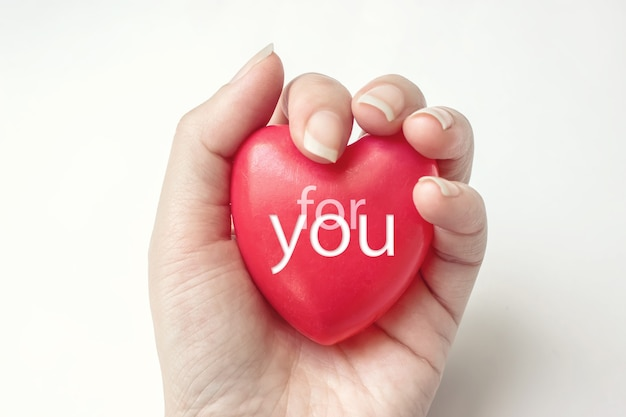 Mano che tiene cuore rosso con testo per te, assistenza sanitaria, donare e concetto di assicurazione familiare.