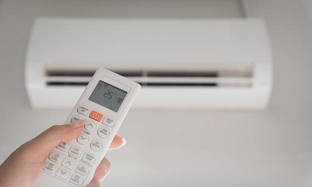 Mano che tiene il telecomando diretto sul condizionatore d'aria all'interno della stanza e impostato a temperatura ambiente, 25 gradi celsius.