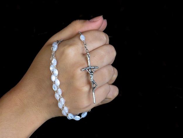Mano che tiene il rosario con sfondo nero e spazio per il testo