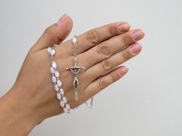 Mano che tiene il rosario con sfondo chiaro e spazio per il testo
