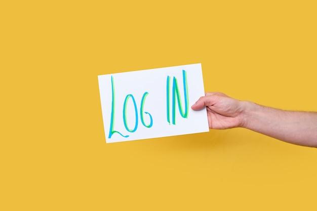Una mano che tiene un cartello con la frase scritta a mano log in