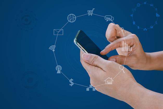 Mano che tiene smart phone con social media sfocati e icone tecnologiche su sfondo blu.