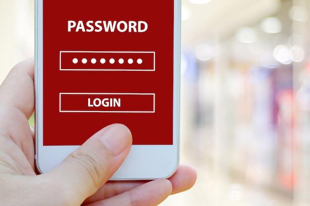 Passi lo smart phone della tenuta con accesso di parola d'accesso sullo schermo sopra il fondo della sfuocatura