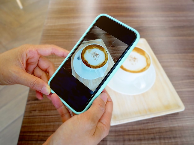 Mano che tiene smartphone e scattare foto di un cappuccino