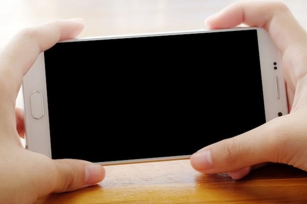 Mano che tiene smartphone con sfondo bianco sullo schermo