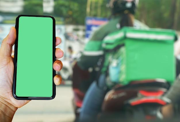 Mano che tiene lo smartphone con l'app food il motociclista sfocato consegna urgentemente cibo ai clienti che ordinano online.