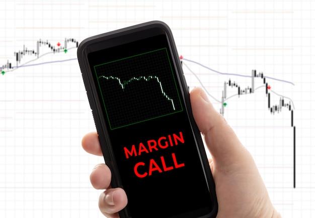 Mano che tiene uno smartphone con la chiamata a margine del messaggio. borsa di perdita di negoziazione. conto di intermediazione