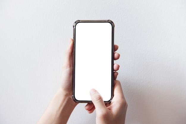 Mano che tiene smartphone con schermo bianco su sfondo bianco