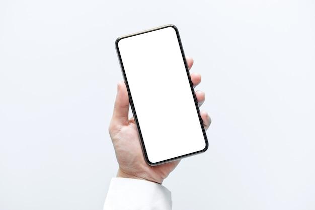 Mano che tiene smartphone con schermo bianco