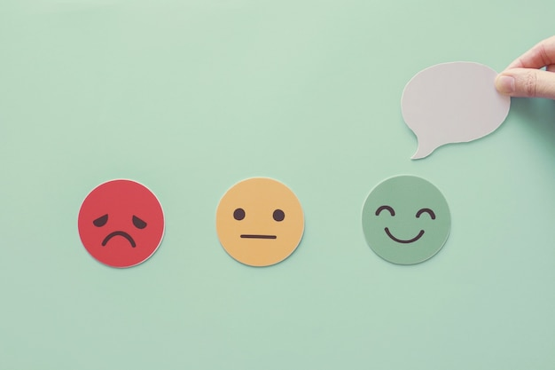 Mano che tiene il fumetto sulla faccia felice, recensione positiva del cliente, valutazione della salute mentale