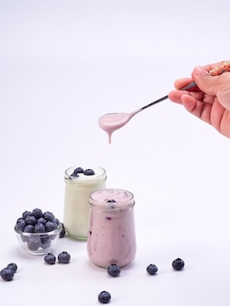 Mano che tiene un cucchiaio con yogurt ai mirtilli