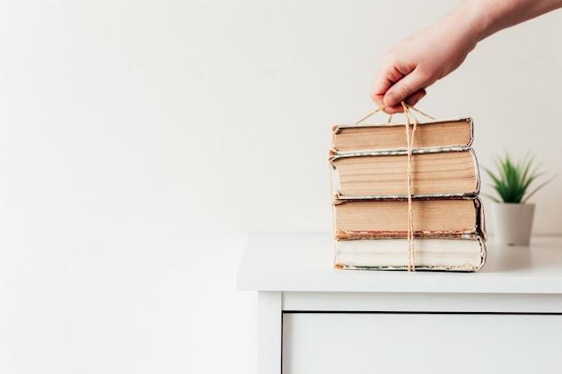 Mano che tiene una pila di vecchi libri in biblioteca, concetto di apprendimento, studio ed educazione, concetto di scienza, saggezza e conoscenza. Foto Premium