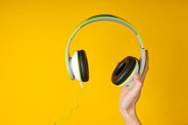 Mano che tiene le cuffie stereo su una superficie gialla
