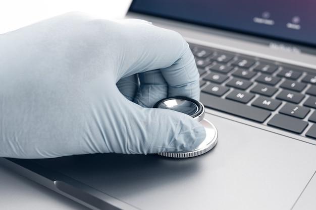 Mano che tiene uno stetoscopio su un moderno computer portatile tecnico che controlla i problemi del computer concept