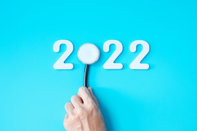 Stetoscopio della tenuta della mano con il numero 2022 su fondo blu. felice anno nuovo per l'assistenza sanitaria, l'assicurazione, il benessere e il concetto medico