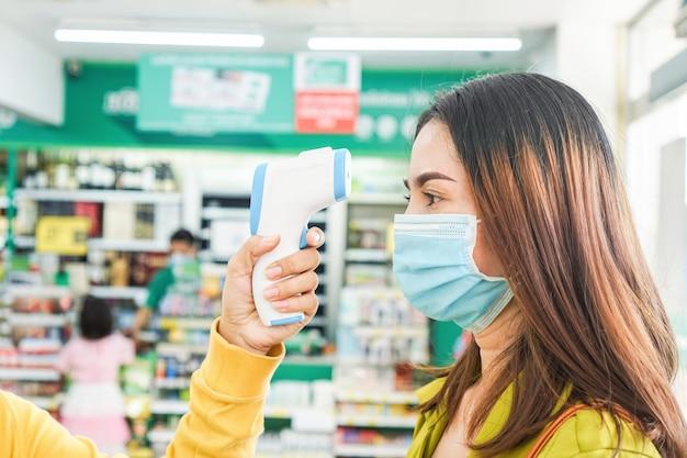 Scanner di temperatura della tenuta della mano che controlla febbre al supermercato