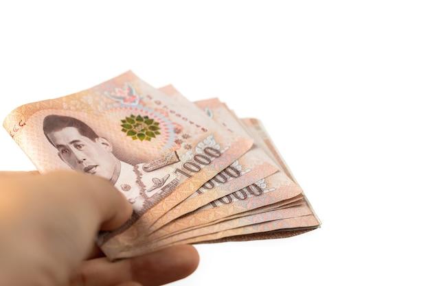 Mano che tiene la valuta tailandese, 1000 baht, banconota dei soldi della thailandia sul muro bianco per il concetto di affari e finanza