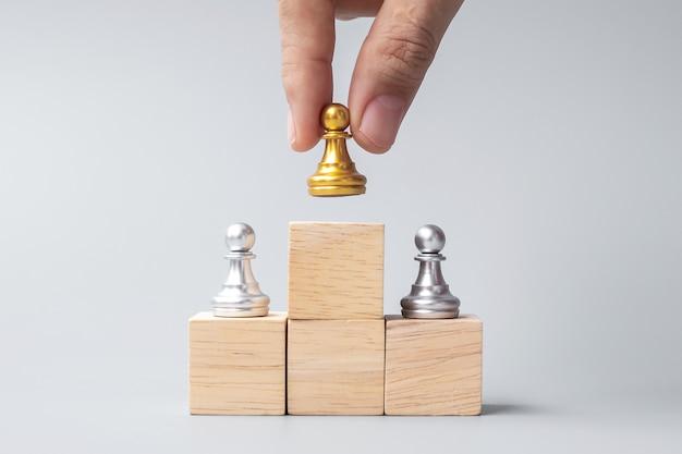 Mano che tiene la parte superiore delle pedine degli scacchi dorate o dell'uomo d'affari leader. vittoria, leadership, successo aziendale, squadra, reclutamento e concetto di lavoro di squadra