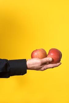 Mano che tiene una mela due su sfondo giallo