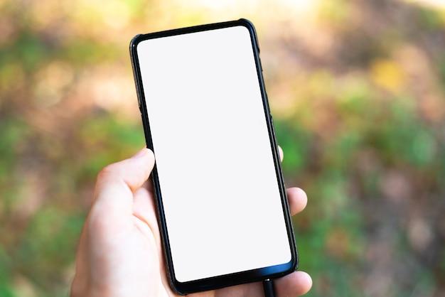 Mano che tiene e utilizzando un telefono cellulare con schermo vuoto bianco