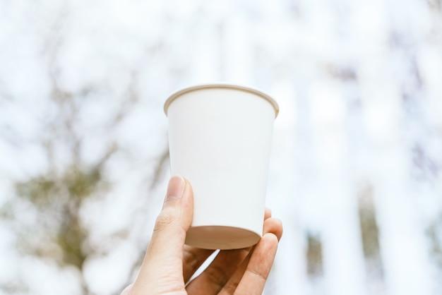Mano che tiene carta da asporto in bianco bianco, cartone o tazza di caffè in cartone con sfocatura.