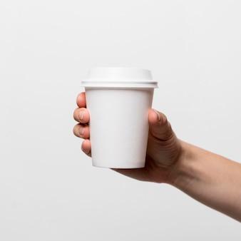 Mano che tiene il primo piano della tazza di caffè bianco
