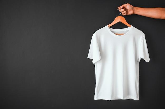 Mano che tiene una maglietta di colore bianco appesa a una gruccia di legno su uno sfondo di colore nero