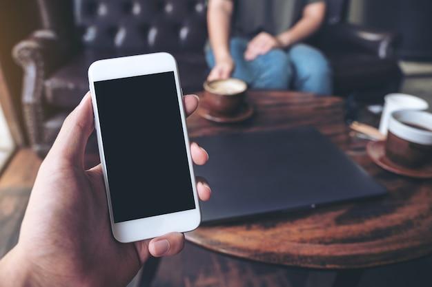 Mano che tiene il cellulare bianco con schermo nero bianco nella caffetteria